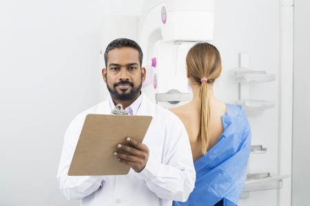 Confident Doctor Holding Clipboard While Patient Undergoing Mamm Archivio Fotografico