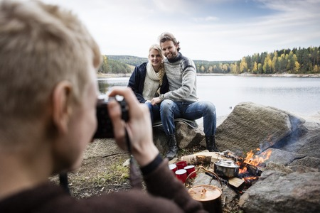 staycation: Man Photographing Couple At Lakeside Camping Stock Photo