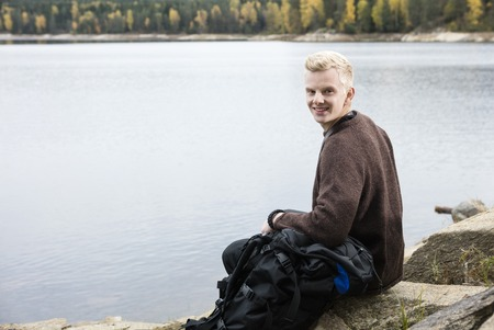 staycation: Happy Male Hiker Sitting On Lakeshore