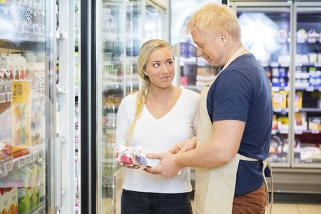 Customer Looking At Salesman Assisting Her In Supermarket Archivio Fotografico