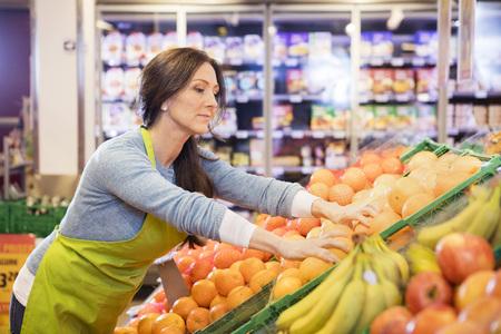 Saleswoman Arranging Oranges In Supermarket