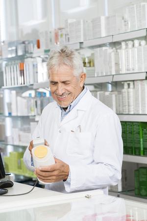 Senior Pharmacist Scanning Barcode Of Shampoo Bottle At Counter
