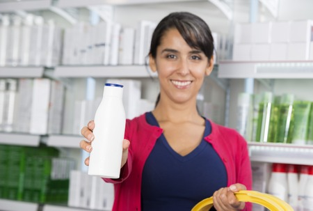 Woman Recommending Shampoo In Pharmacy Stock Photo