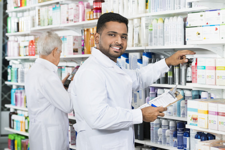 Smiling Chemist Counting Stock With Colleague In Pharmacy Stock Photo