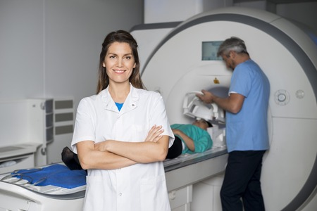resonancia magnetica: Smiling Doctor With Colleague Preparing Patient For CT Scan