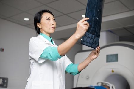Doctor que examina la radiografía mientras que paciente que miente en la máquina de la exploración del CT