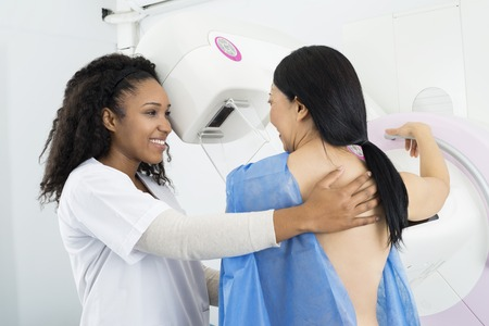 Happy Doctor Assisting Woman Undergoing Mammogram X-ray Test