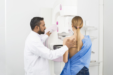 Doctor Standing Assisting Patient Undergoing Mammogram X-ray Tes