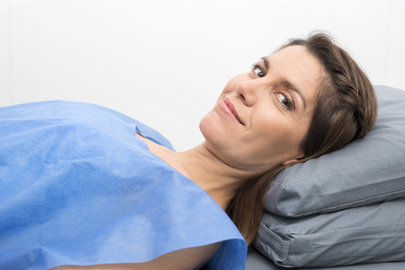 Female Patient In Protective Clothing Lying On Hospital Bed Stock Photo