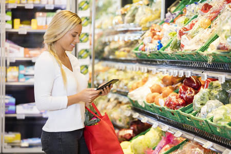 Woman Using Digital Tablet In Grocery Store