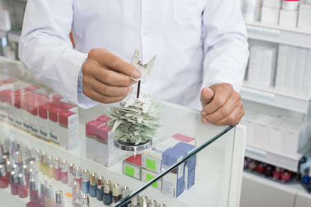 Chemist Inserting Tags In Holder At Counter In Pharmacy