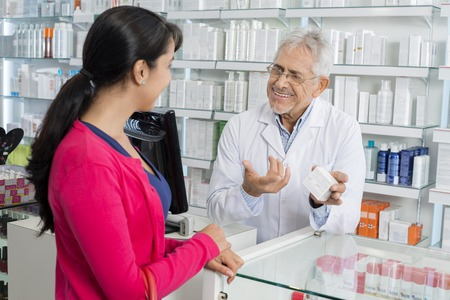 Chemist Gesturing While Communicating With Female Customer Stock Photo