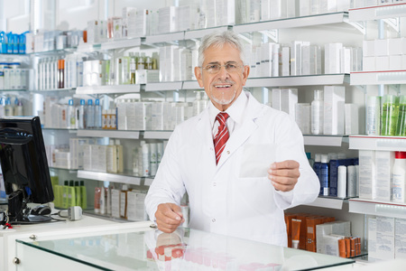 Male Chemist Looking At Prescription Paper At Counter