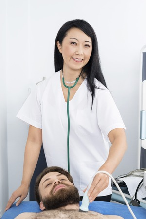Happy Doctor Performing Ultrasound Test On Patient