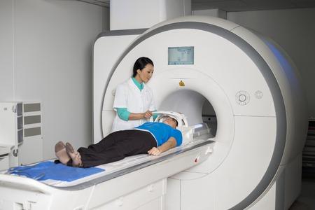 Doctor Fixing Mask To Patient que miente en la máquina de la exploración del CT