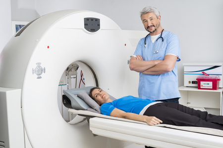 Doctor Standing Arms Crossed By Patient Lying On MRI Machine