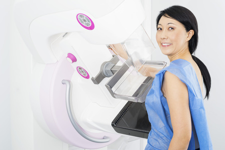 Smiling Woman Undergoing Mammogram X-ray Test Stock Photo