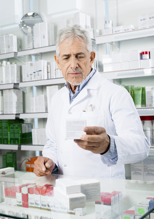 Chemist Holding Medicine At Counter In Pharmacy Archivio Fotografico