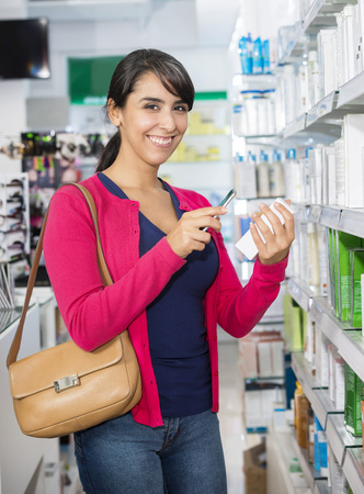 Woman Scanning Barcode Through Smart Phone In Pharmacy