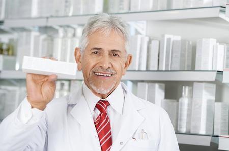 Pharmacist Smiling While Holding Medicine Box