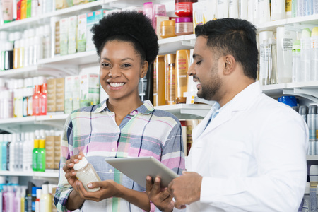 Customer Holding Product While Standing By Chemist Stockfoto