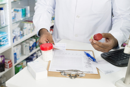 Pharmacist With Pill Bottles And Clipboard At Counter
