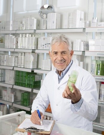 Male Pharmacist Holding Product While Writing On Clipboard Archivio Fotografico