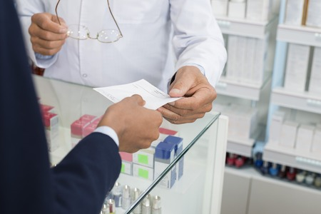 Cropped Image Of Businesswoman Showing Prescription To Chemist Stok Fotoğraf