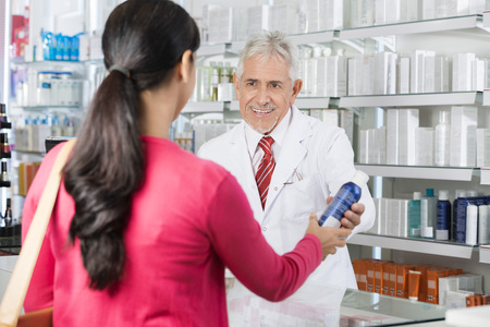 Pharmacist Selling Deodorant Bottle To Woman Archivio Fotografico