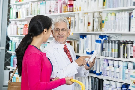 Chemist Looking At Customer While Pointing At Shampoo Bottle Archivio Fotografico