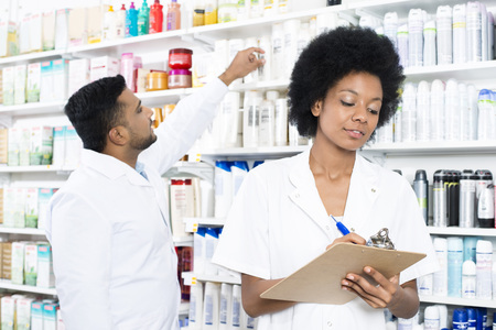 Chemist Writing On Clipboard While Colleague Arranging Products Stock Photo