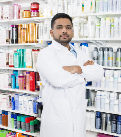 Pharmacist Standing Arms Crossed By Shelves In Drugstore