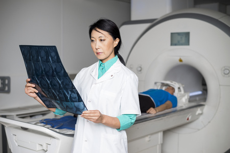 Doctor Analyzing X-ray While Patient Lying On CT Scan Machine