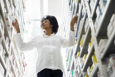 Young Female Chemist Arranging Stock In Shelves At Pharmacy Stock Photo