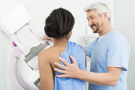 Mature Doctor Assisting Patient Undergoing Mammogram Test