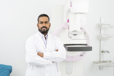 Confident Doctor Standing Arms Crossed By Mammography Machine Archivio Fotografico