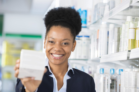 Happy Businesswoman Showing Medicine Box In Pharmacy Archivio Fotografico