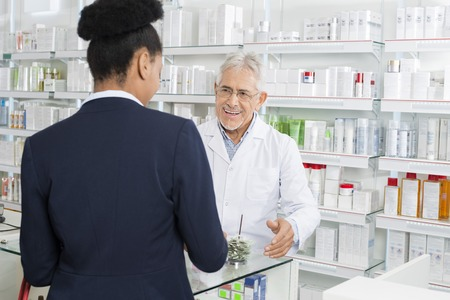 Pharmacist Looking At Businesswoman In Pharmacy