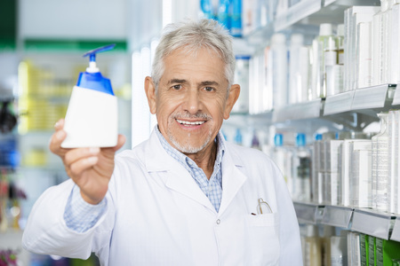 Chemist Holding Soap Dispenser In Pharmacy