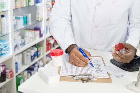 Chemist Holding Pill Bottle While Writing On Paper Archivio Fotografico