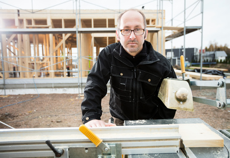 Confident Male Carpenter Using Table Saw To Cut Plank