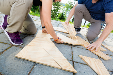 Low Section Of Friends Solving Wooden Planks Puzzle On Patio