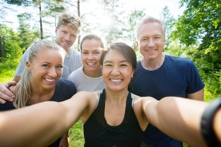 Portrait of happy mature woman taking selfie with friends in forest