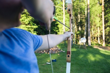 Midsection of mature male athlete aiming arrow at target board in forest