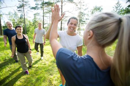 Vrouwen geven hoge vijf terwijl vrienden lopen in het bos Stockfoto