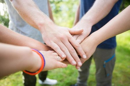 Closeup Of Friends Stacking Hands In Forest