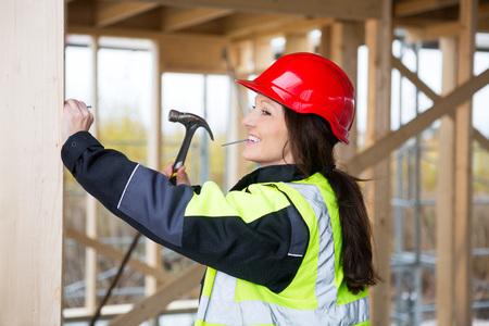 Smiling Female Carpenter Hammering Nail In Wood At Site