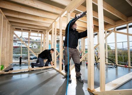 Professional Carpenters Drilling Wood At Site