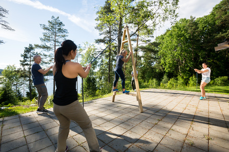 Friends Pulling Ropes To Balance Woman On Wooden Structure