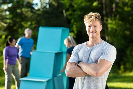 Smiling Young Man Standing Arms Crossed While Friends Making Pyr